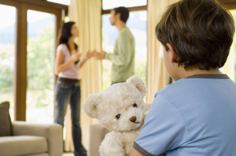 Boy with teddy bear and parents fighting