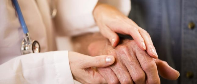 female-doctor-holding-old-persons-hand-646x275