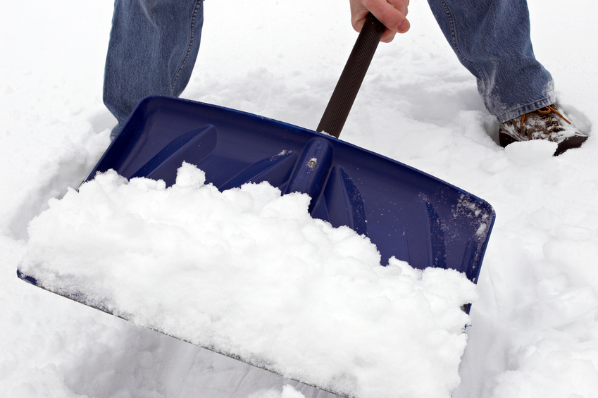 Closer view of a man shoveling snow